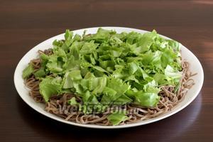 Сверху выложить листья салата и немного зеленого лука.