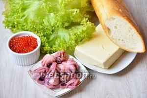 Для того чтобы приготовить вкусные бутерброды с осьминогами и красной икрой понадобится сливочное масло, осьминоги, батон, листья салата и икра красная.