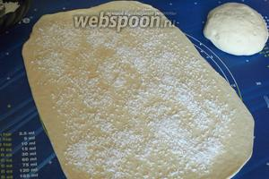 Подошедшее тесто обмять, разделить на 2 части. Раскатать тонко в прямоугольник одну часть теста, смазать подсолнечным маслом и посыпать кокосовой смесью.