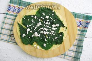 На блин выкладываем листики крапивы и посыпаем крошками брынзы.