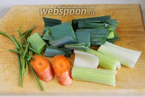 Приготовить овощи для бульона: крупно нарезать зелень порея, стебель сельдерея, морковь, стебли зелени.