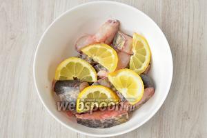 Кладу нарезанный кусок лимона кладу в глубокую тарелку с рыбой.