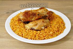 Готовый рис высыпаем на тарелку для подачи, сверху выкладываем кусочки курицы.