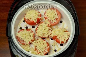 Устанавливаем корзинку-пароварку в мультиварку над подготовленной чашей с гречкой, посыпаем помидоры сыром, закрываем крышку и включаем программу «Плов» на 1 час по умолчанию.