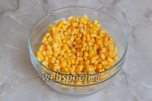 Прежде всего поставим вариться яйца и займёмся остальными ингредиентами. Открываем банку с кукурузой и сливаем жидкость. Перекладываем кукурузу в салатник.