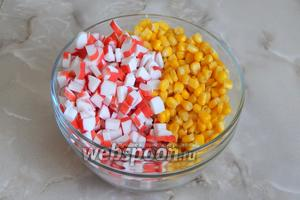 Крабовые палочки, если они были замороженные, предварительно заморожены — разморозим. Нарежем их размером примерно с кукурузу и добавим в салатник.