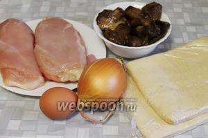 Для приготовления слоёных пирожков взять упаковку слоёного дрожжевого теста, солёные лесные грибы, куриное филе, лук, масло, яйцо.