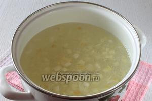Бульон процедить. Положить лук в бульон. Рис хорошо промыть, всыпать в бульон и поставить варить.