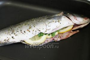 Внутрь рыбы уложить лимон и петрушку и выложить рыбу в форму для запекания. Полить сверху маринадом от рыбы.