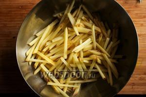 Насыпьте картофельную соломку в большую миску.