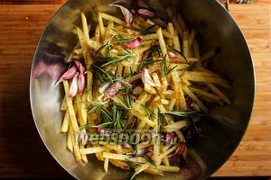 Картофель посолите, поперчите, добавьте розмарин и зубчики чеснока, перемешайте.