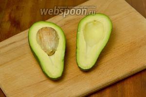Разрезаем авокадо на две половинки, обведя ножом косточку, а затем повернув половинки в разные стороны, чтобы они разъединились.