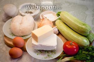 Для приготовления пирога с куриным филе, кабачками и творогом нам понадобятся: отварное куриное филе, кабачки, творог, молоко, твёрдый сыр, яйца, мука, лук, чеснок, помидор, зелень, морская соль, специи, растительное масло для жарки.