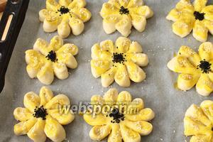 Выкладываем все изделия на противень, смазываем желтком, который мы отложили в сторону (взболтать его со столовой ложкой растительного масла). В центр присыпаем чёрный кунжут, на «лепесточки» белый.