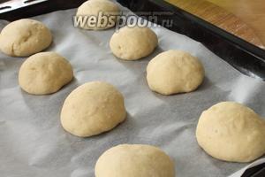 Подошедшее тесто выкладываем на стол, присыпанный мукой и слегка обминаем. Делим тесто на равные по размеру кусочки величиной чуть больше яйца и формируем аккуратные шарики.