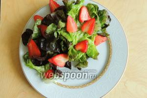 Салат нарвём на большие куски и кладём в тарелки. Сверху кладём нарезанную клубнику.