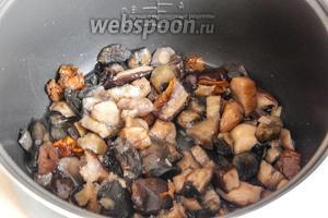 Грибы можно использовать свежие — их нужно перебрать и отварить. У меня этот этап пройден — только разморозим их. Наливаем в чашу мультиварки масло, кладём грибы и готовим на режиме Жарка или Выпечка, пока не выпарится влага и грибочки не зарумянятся.