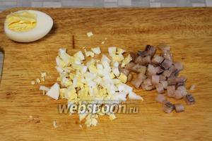 Мелко порезать несколько ломтиков сельди и половинку яйца.