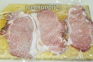 Прикрыть мясо пищевой плёнкой и отбить с двух сторон кухонным молоточком.