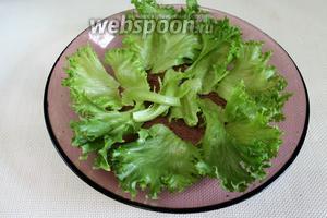 Сочные салатные листья крупно порвать и устелить ими дно салатника.