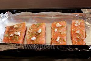 Рыбу выложить на лист фольги кожей вниз, предварительно смазав фольгу маслом. Зубчики чеснока раздавить и выложить поверх рыбы. Полить оставшимся маринадом. Поставить запекать в разогретую до 180ºC духовку. Степень запекания рыбы отслеживайте по своему вкусу.