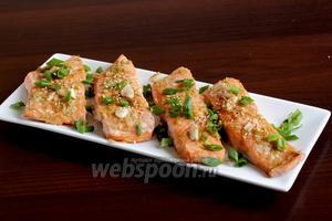 Готовые кусочки рыбы легко отделяются от кожи, кожица остаётся на фольге, а рыбу можно выложить на блюдо. Посыпать зелёным луком и кунжутом. Подавать хорошо с овощами.