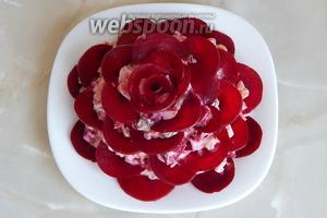 Выкладываем полукруги из свёклы на салат, имитируя лепестки розы. Делать это лучше снизу вверх. На самом верху стараемся скрутить лепестки в бутон.