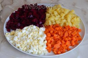 Остужаем овощи и яйца, очищаем их и нарезаем некрупными кубиками одинакового размера. Одну свёклу оставляем для декора.