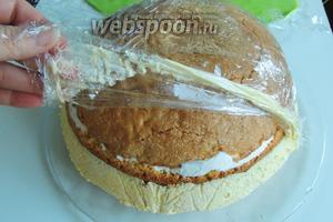 Кладём сверху на форму с тортом блюдо для торта, прижимаем с обеих сторон руками и переворачиваем торт на блюдо. Освобождаем от пищевой плёнки.