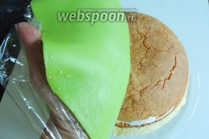 Верхний слой плёнки снимаем с марципа, держим руками снизу и переворачиваем, покрывая торт.