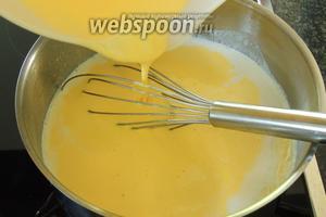 В молоко тонкой струйкой вливаем смесь желтков с крахмалом, помешивая венчиком.