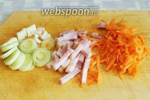 Нарезать белую часть лука-порея, кусочек стебля сельдерея, копчёную грудинку, натереть на тёрке морковь.