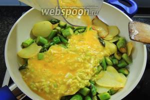 Выливаем яйца на картофель со спаржей, сразу же перемшаем, уменьшим огонь до малого, накроем крышкой и готовим около 15 минут.