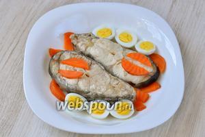 Раскладываем отваренные половинки перепелиных яиц и нарезанную полукольцами морковь.