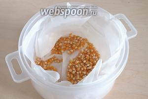 Возьмите пластиковый контейнер, имеющий крышку с клапаном и подходящий для использования в СВЧ. Насыпьте на дно кукурузу в один слой. Форму предварительно лучше выстлать пекарской бумагой. Закройте крышку, откройте клапан. Готовьте в СВЧ на максимальной мощности от 1,5 до 2,5 минут. Ориентируйтесь на слух, когда зёрна начнут «взрываться» всё реже и реже, попкорн готов.