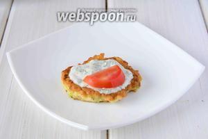 На сервировочную тарелку, выкладываем один оладий, смазываем его сметанным соусом. Помидоры порезать кружочками. Один кружочек помидора выложить сверху на оладий.