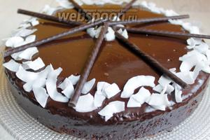 Весь ганаш выливаем прямо на середину торта. Не размазываем. Аккуратно поворачиваем блюдо и он сам растекается. Потом помогаем лопаткой стечь ганашу по бокам. Даём остыть. И украшаем. У меня кокосовые чипсы и шоколадные палочки.