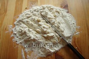Для начала высыпаем муку с солью на стол, сверху выкладываем масло и рубим его ножом в мелкую крошку.