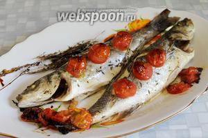 Подавать рыбу на блюде, украсив половинками запечённых помидоров и дольками лимона.
