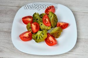 Далее раскладываем на большую тарелку ингредиенты. На первый слой кладём брокколи и помидоры.