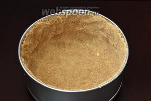 Форму диаметром 18 сантиметров выложить кулинарной бумагой и по дну и бокам распределить крошку из печенья. Хорошо прижать ко дну и стенкам формы. Поставить в холодильник на 30 минут.