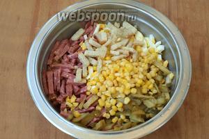 Соединить в миске яйца, колбасу, огурцы, сухарики и кукурузу. Немного сухариков отложить.