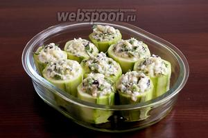 Нафаршировать кабачки полученной смесью и выложить их в форму. Сбрызнуть оливковым маслом и запекать в духовке при 180ºC 30 минут. Верх должен зарумяниться.