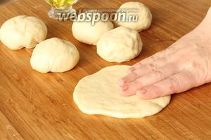 Подошедшее тесто выложить на стол и слегка обмять.   Руки чуть смазать растительным маслом и отрывая от теста кусочки, сформировать из них шарики. Руками расплющить каждый шарик в лепёшку ( 0,5 см).