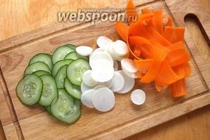 Нарежьте огурцы и дайкон очень тонкими кружочками, нарежьте морковку с помощью «экономки» тонкой длинной стружкой.