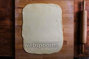 Возьмите большую часть и раскатайте в прямоугольник. Подгоняйте его по размерам к противню на котором вы будите печь пирог. Пласт должен получиться на 2-3 см длиннее противня.