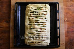 Накройте пирог крышкой, расправьте, если она получилась более длинной, обрежьте лишнее. Немного прижмите края пирога, чтобы запечатать его и смажьте взбитым яйцом. Дайте пирогу постоять 20 минут, а затем отправьте пирог в духовку разогретую до 220-230 °C.