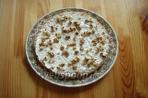 Сверху промазываем кремом и выкладываем рубленные грецкие орехи. Так поступаем и со вторым коржом.