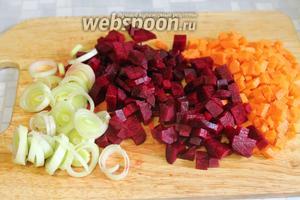 Мелкими кубиками порезать морковь и свеклу, тонкими колечками белую часть порея.