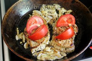 На поверхность котлет выложить дольки помидора, нарезанного наискось — если кружками, то он просто сварится и растечётся, а так останется целым и словно запечённым.